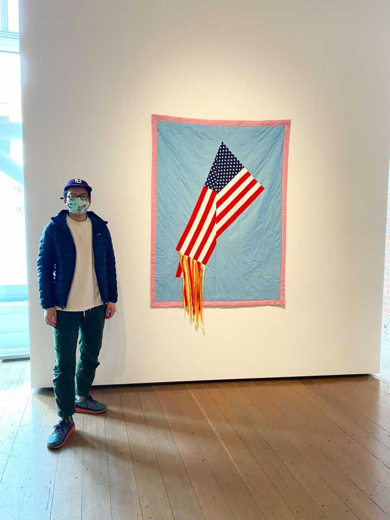 Person wearing a mask and hat standing next to a quilt of the American flag on fire